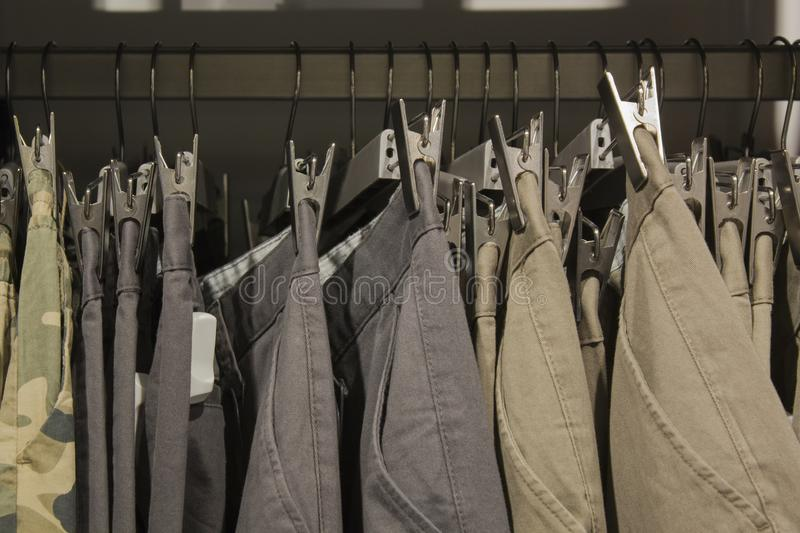 Many trousers hanging on a rack. Row of pants in closet. concept of buy , sell and shopping stock photo