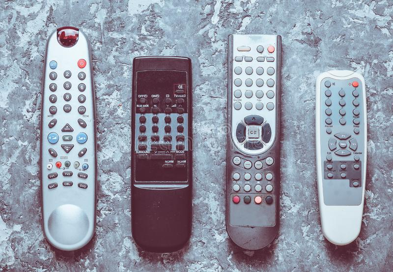 Many TV remotes on a gray concrete table. Top view. Remote control of home appliances and electronics. stock image