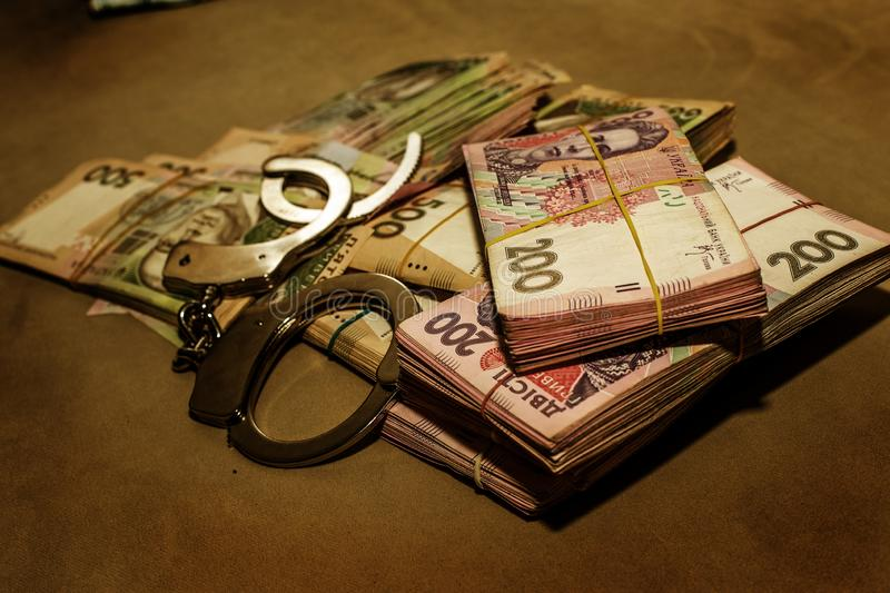 Many Ukrainian money hryvnia. Handcuffs on the money. Corruption in Ukraine. The fight against corruption. Physical evidence of. Corruption in government and stock photos