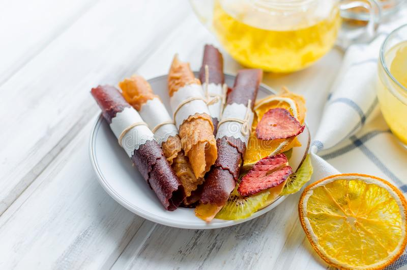 Many variety fruit leather rolls and chips and glass cup and teapot of sea buckthorn tea on breakfast on white wooden table,. Natural light, selektive focus royalty free stock photography