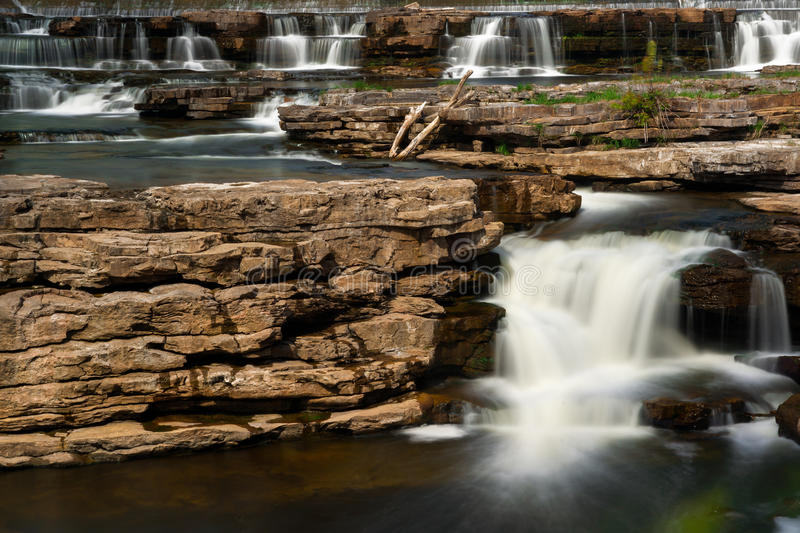 Many Waterfalls Cascading over Rocks. Beautiful scenery of many multiple waterfalls flowing and cascading over a rocky area, captured in a timed exposure stock photography