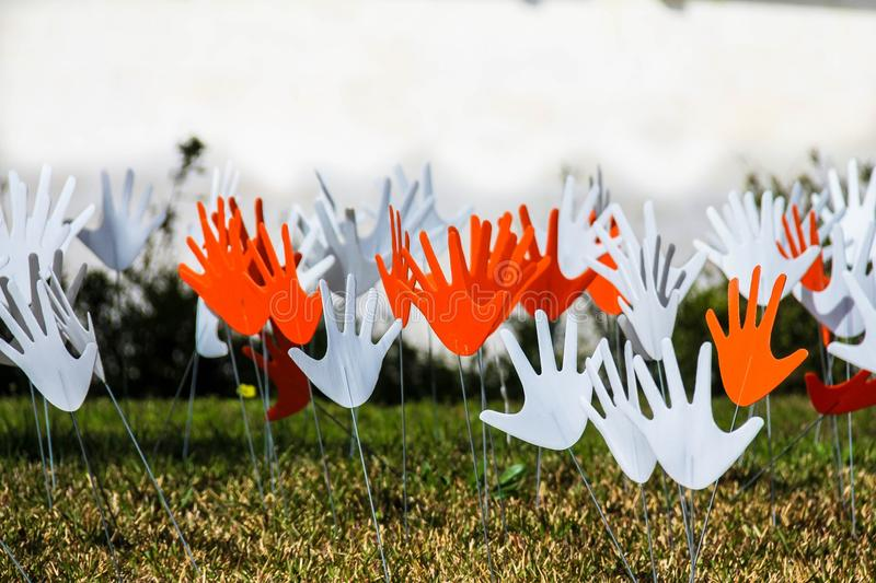 Many waving abstract hands signs or flags installed on a grassy lawn stock image