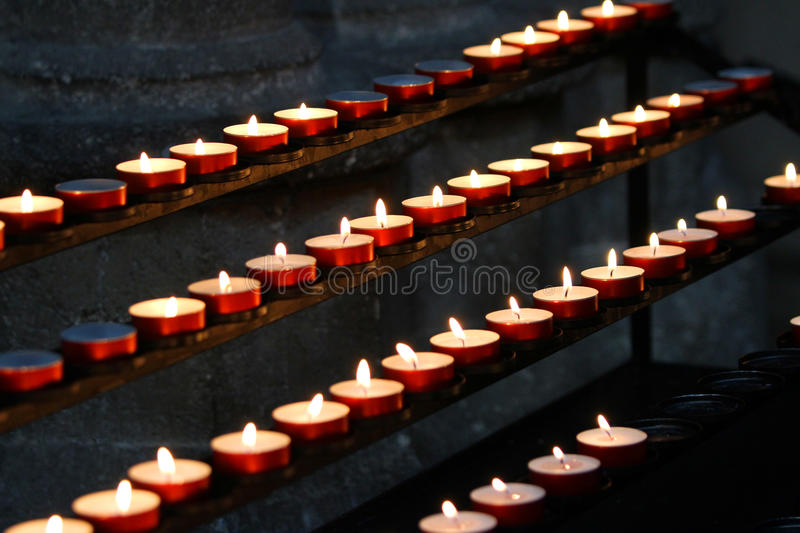 Many wax candles lit by old faithful. Candlestick in church with many wax candles lit by old faithful royalty free stock image