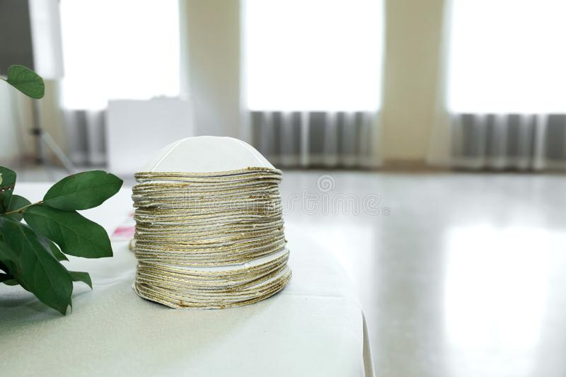 Many white gold-plated Jewish Kippa headdresses stacked on the table.  stock images