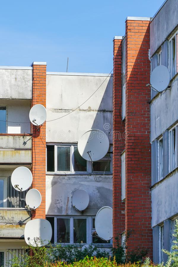 Many white parabolic satellite antenna dishes hanged on wall of suburban perfab block of flats stock image