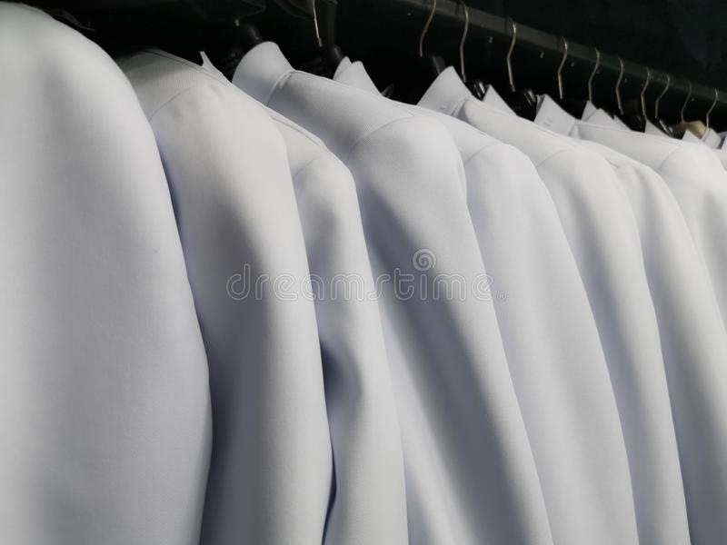 Many white shirts hanging from the clothes rack, Wedding dress rental. Background, business, care, chemical, clean, client, clothing, color, conditions, cotton stock photo