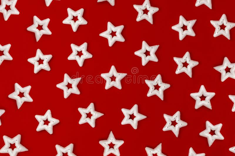 Many white stars on a bright red background. Pattern of Christmas decorations stock photography