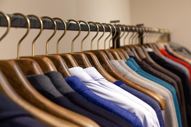 Many wooden hangers with different male clothes in boutique on metal stand. Closeup, side view. Concept opening of luxury business stock images