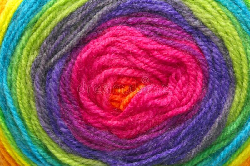 Woolen threads wrapped around each other to form a target with t. Many woolen threads wrapped around each other to form a colored target with the colors of the royalty free stock image