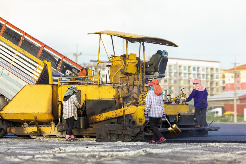 Many workers with equipment helped to build or paver the road with asphalt compactor finisher machine in the afternoon royalty free stock photos