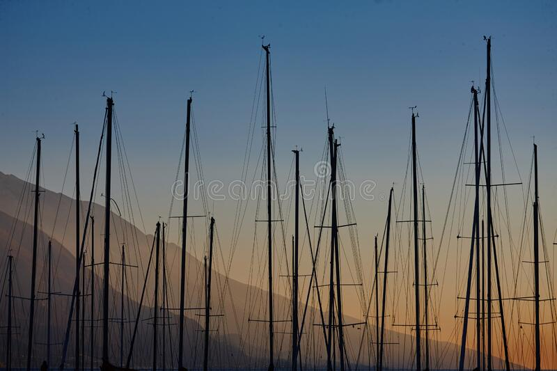 Many yacht masts in the port against the backdrop of a beautiful sunset royalty free stock photo