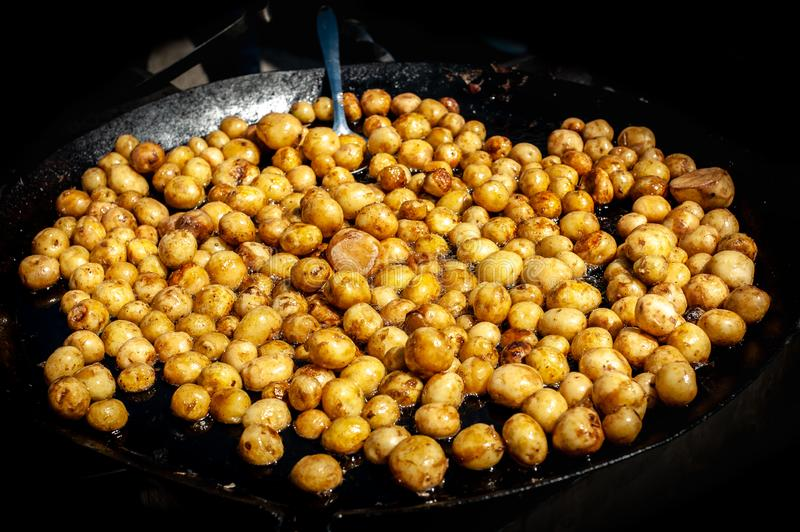 Many of yellow small solid and not sliced potatoes glossed from oil,  frying on big black pan, black isolated stock photography