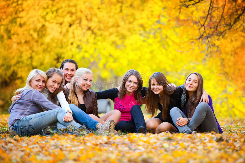 Many young girls in the autumn park. Sitting on the grass royalty free stock photos