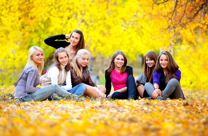 Many young girls in the autumn park. Sitting on the grass stock images