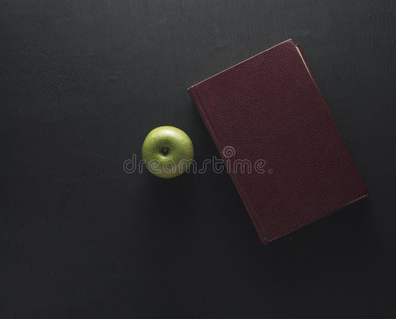 Manzana del verde de la visión superior con el libro viejo en fondo de madera negro sch imagen de archivo