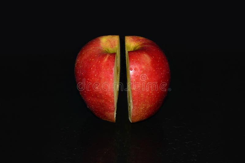Manzana hermosa en un fondo negro con una superficie del espejo imagen de archivo