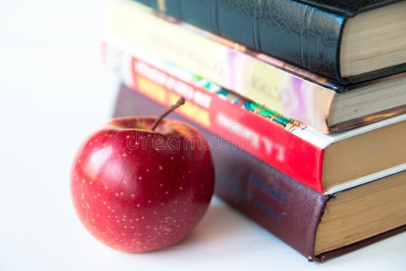 Manzana jugosa madura roja cerca de los libros stock de ilustración