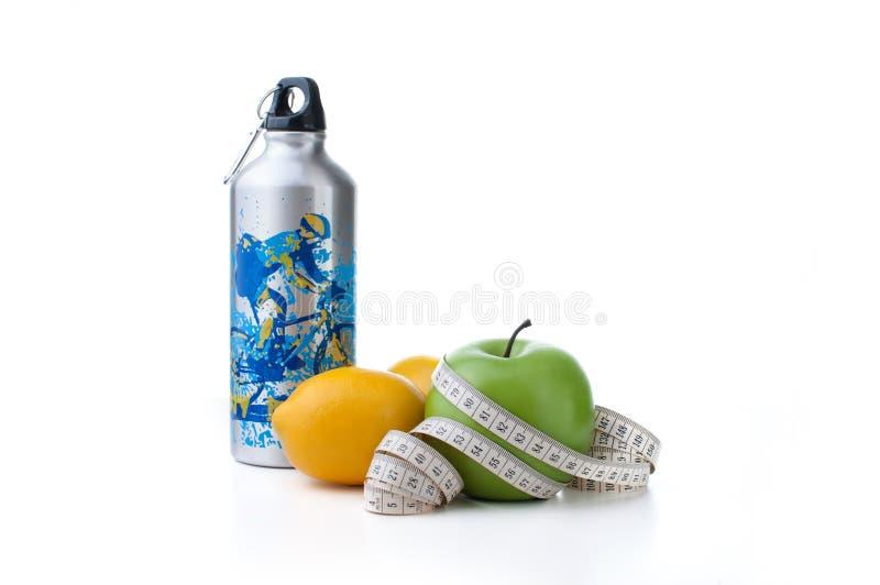 Manzana, limón y botella verdes del deporte con la cinta métrica imagenes de archivo