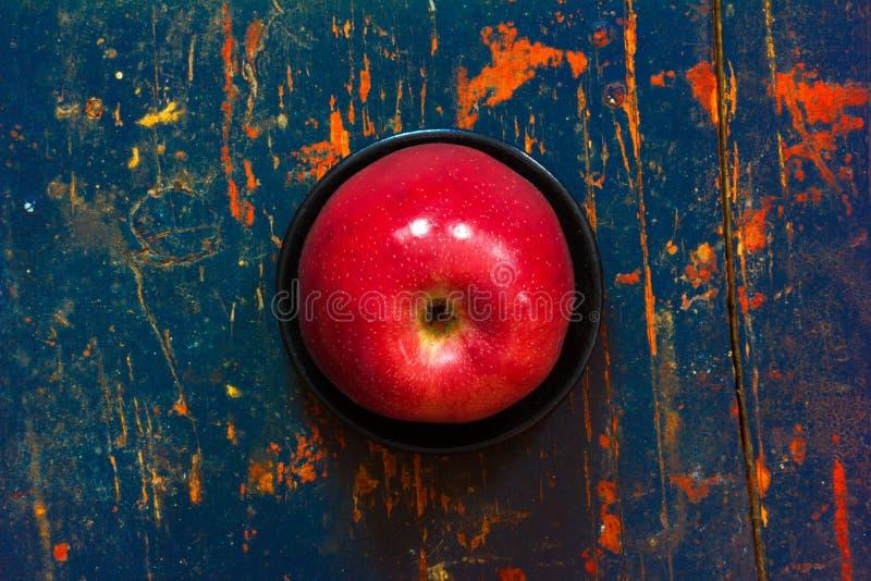 Manzana madura roja en un platillo negro en viejo fondo fotos de archivo libres de regalías