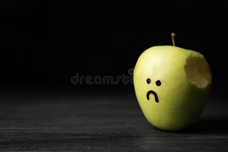 Manzana mordida con el dibujo de la cara infeliz en la tabla contra el fondo oscuro, espacio para el texto fotos de archivo libres de regalías