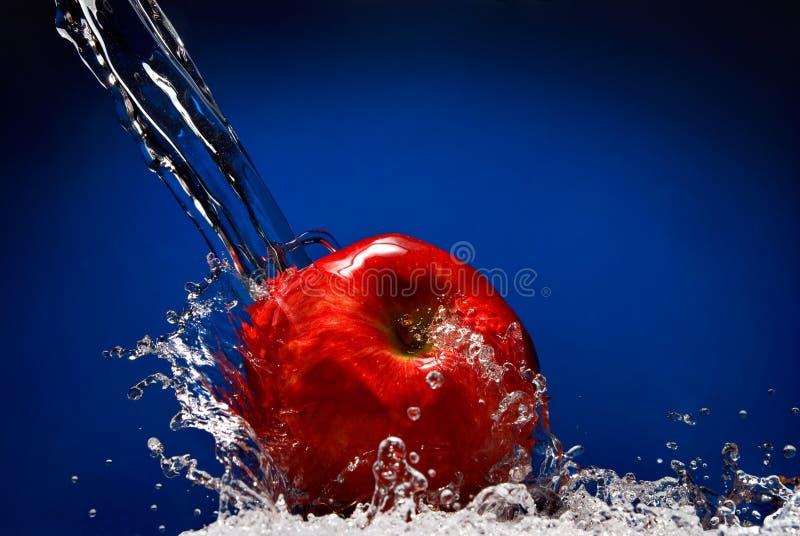 Manzana roja con el chapoteo del agua imágenes de archivo libres de regalías