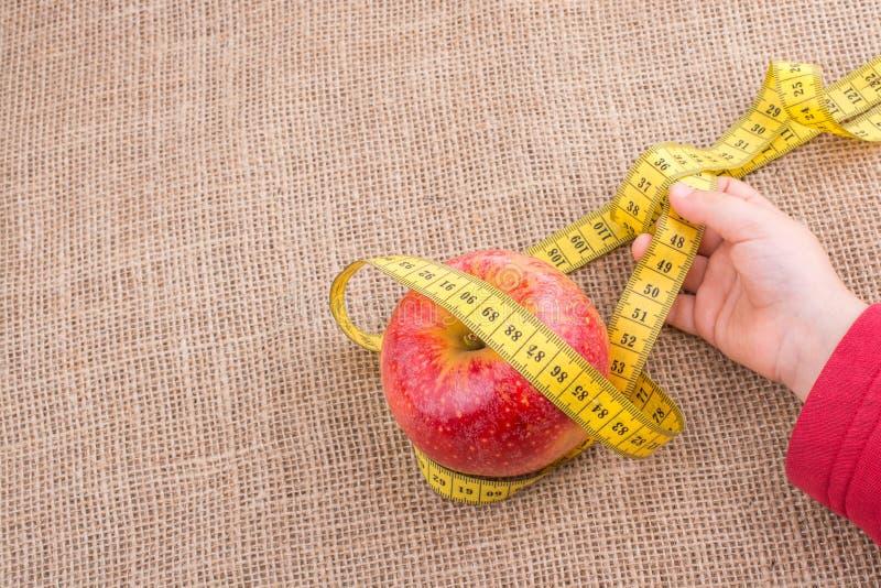 Download Manzana Roja Con Una Cinta De La Medida En Ella Foto de archivo - Imagen de salud, caloría: 100532814