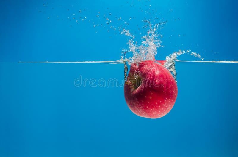 Manzana roja en el agua con un chapoteo en fondo azul imagen de archivo