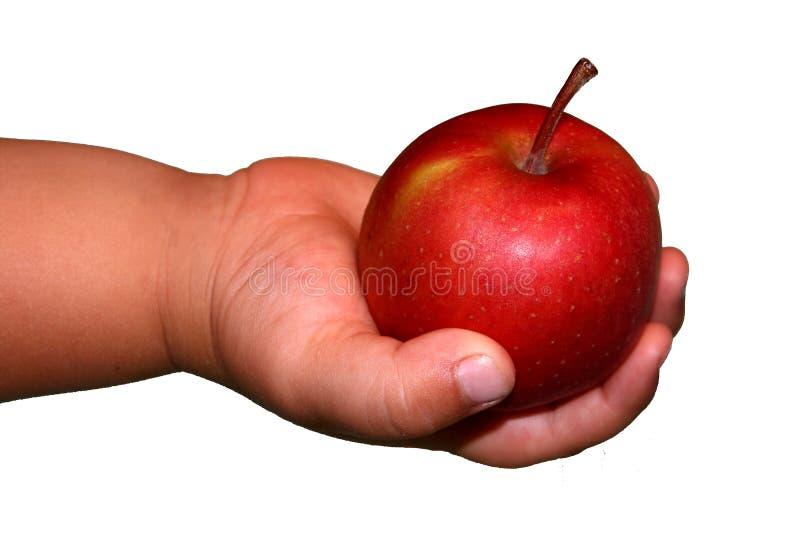 Manzana roja en la mano del niño imagenes de archivo