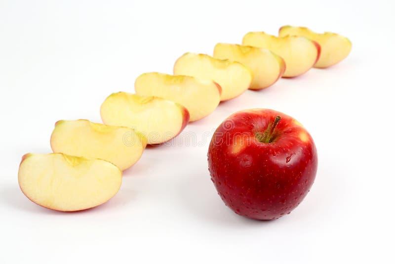 Manzana roja en un fondo de pedazos cortados de manzana fotografía de archivo libre de regalías