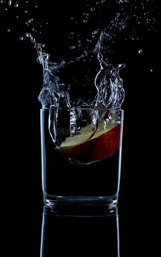 Manzana roja fresca con las gotitas del agua contra la reflexión negra del fondo foto de archivo libre de regalías