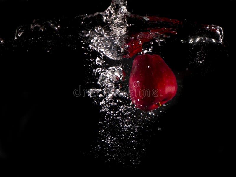 Manzana roja, limón amarillo que cae en salpicar el agua en fondo negro fotos de archivo