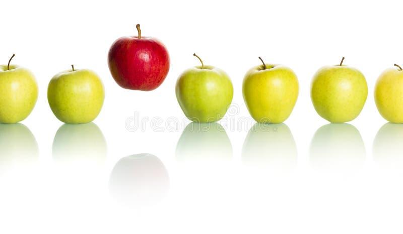 Manzana roja que se coloca hacia fuera de la fila de manzanas verdes. imagen de archivo