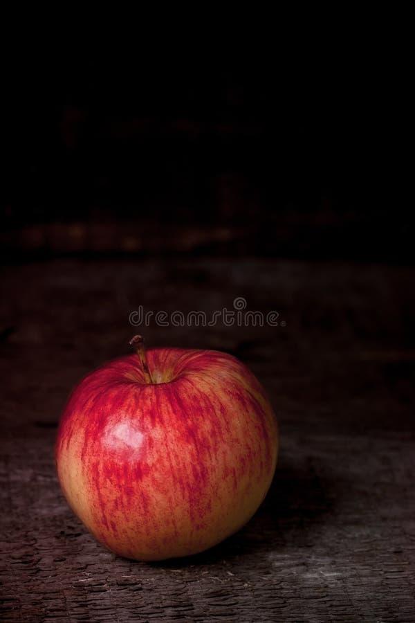 Manzana roja y amarilla en viejo fondo de madera fotos de archivo