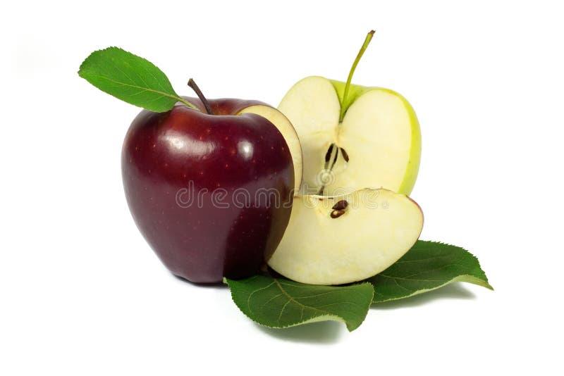 Manzana roja y amarilla fresca con las rebanadas en las hojas del verde aisladas en blanco foto de archivo libre de regalías