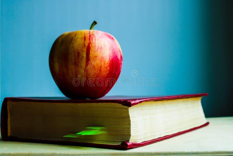 Manzana roja y cierre duro rojo del libro de la cubierta para arriba en fondo azul Apple del conocimiento - met?fora imagenes de archivo