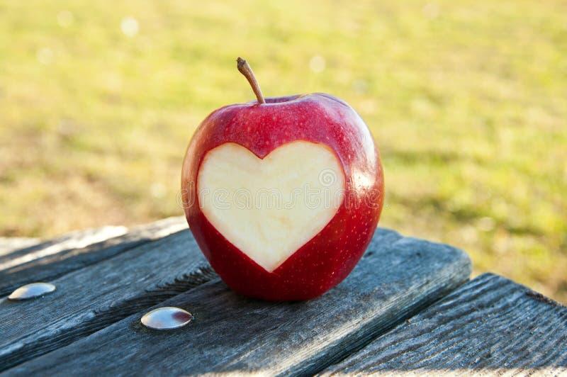 Manzana sola con el corazón tallado fotos de archivo libres de regalías