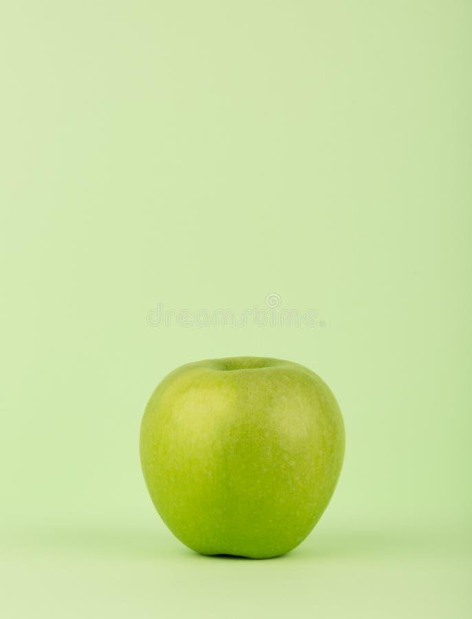 Manzana verde aislada en fondo verde Limpio y fresco Copie el espacio vertical fotografía de archivo libre de regalías