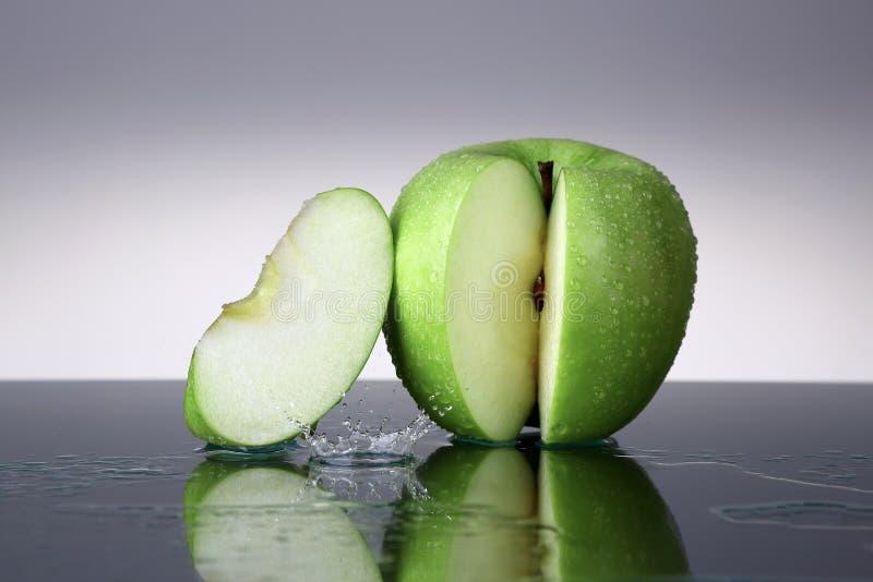 Manzana verde con descenso de la rebanada y del agua imagen de archivo libre de regalías