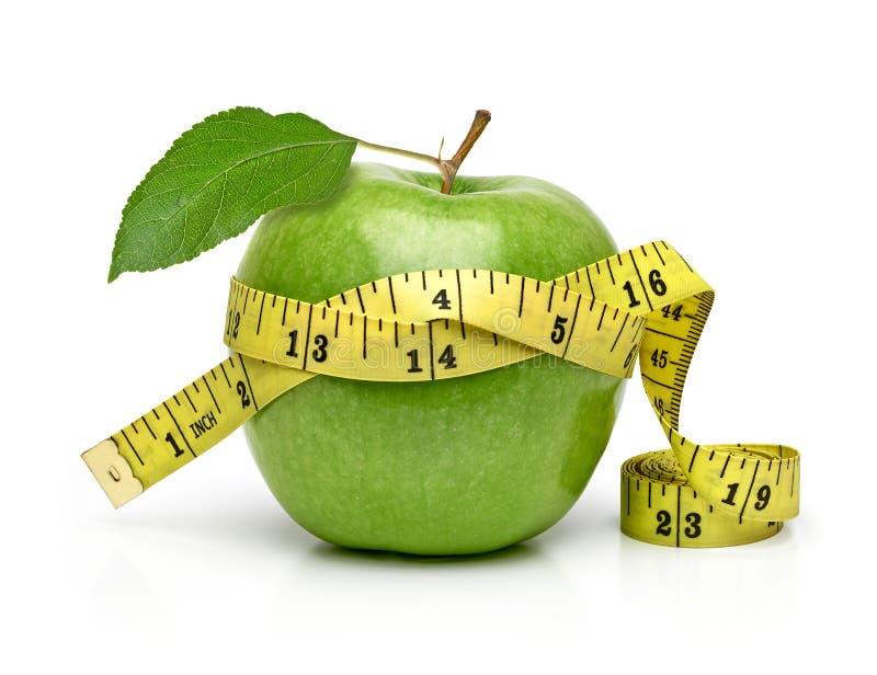 Manzana verde con la cinta métrica foto de archivo