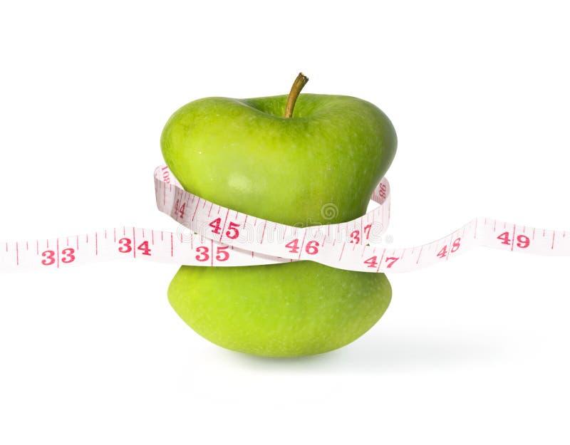 Manzana verde con la cintura y la cinta métrica delgadas fotografía de archivo