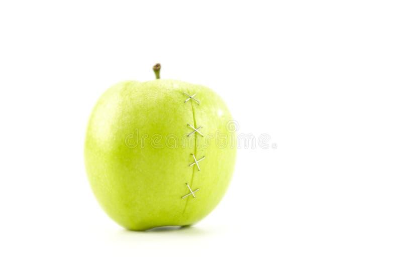 Manzana verde con la grieta sujetada con grapa foto de archivo