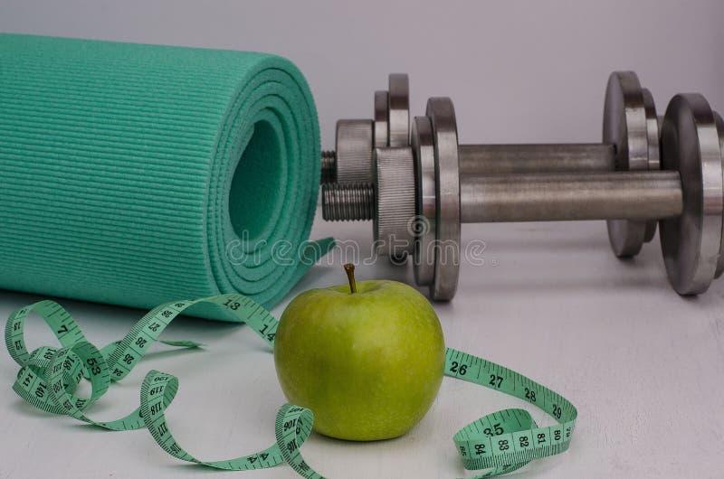 Manzana verde con pesas de gimnasia, una manta y una cinta Aptitud femenina imagenes de archivo