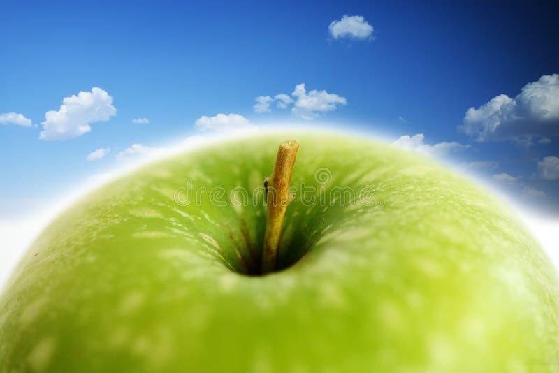Manzana verde contra el cielo azul, imagen compuesta fotografía de archivo