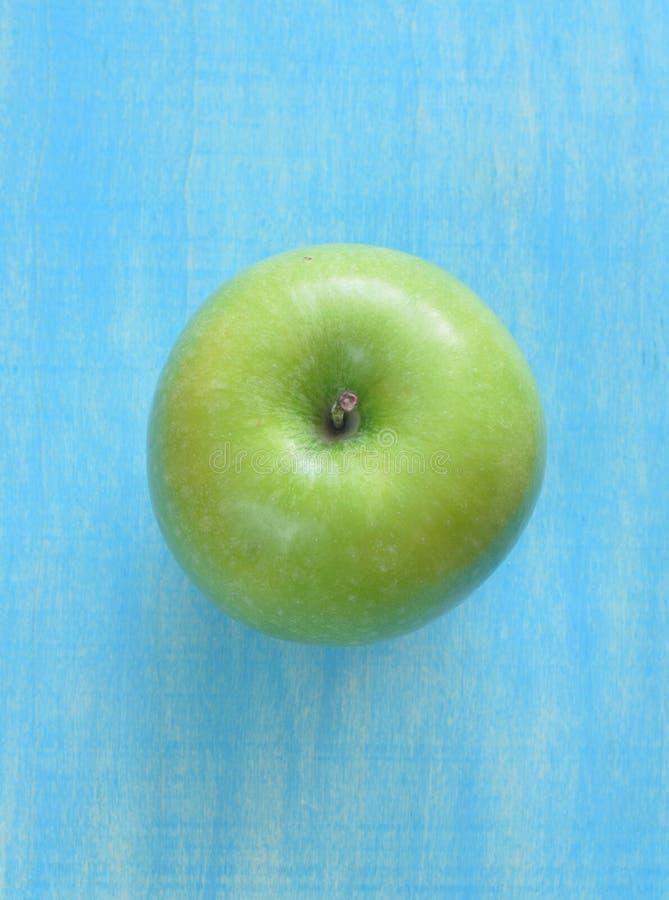 Manzana verde en fondo azul vertical foto de archivo