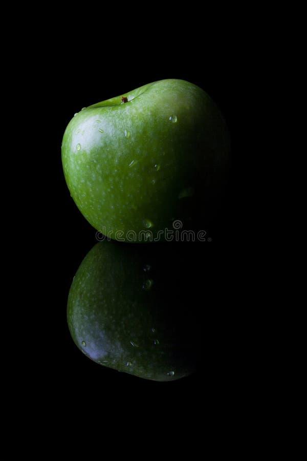 Manzana verde en negro del lado con vertical de la reflexión fotos de archivo