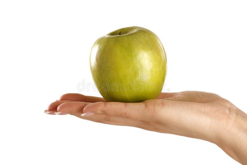 Manzana verde en una mano hermosa femenina imagen de archivo