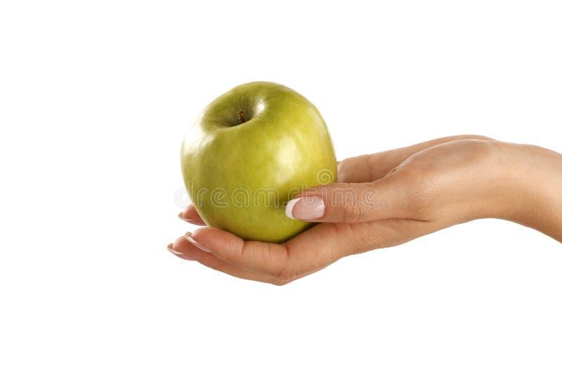 Manzana verde en una mano hermosa femenina fotos de archivo