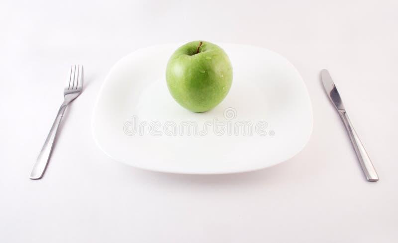 Manzana verde en una placa foto de archivo