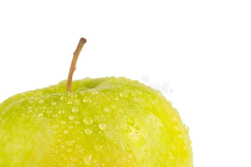 Manzana verde fresca con las gotitas del agua contra el fondo blanco foto de archivo libre de regalías