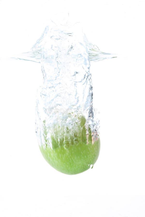 Manzana verde que cae en agua contra el fondo blanco fotografía de archivo libre de regalías